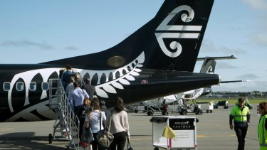 Passengers board an Air New Zealand flight at Christchurch Airport in Christchurch, New Zealand, Wednesday, Sept. 20, 2017. New Zealand's lawmakers and public employees were told to cancel all nonessential flights to and from Auckland as a fuel shortage at the nation's largest airport continued to disrupt the travel plans of thousands of people. (AP Photo/Mark Baker)