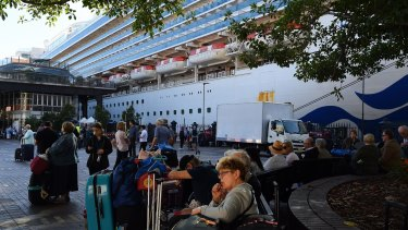 Passengers sit with their luggage after disembarking from the Ruby Princess cruise ship on March 19 at Circular Quay, Sydney.