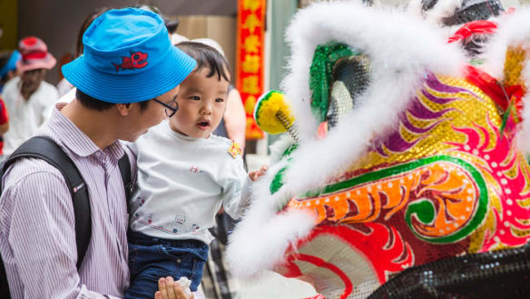 A Chinese dragon greets Timmy Yang Yang, 2, at the National Multicultural Festival.