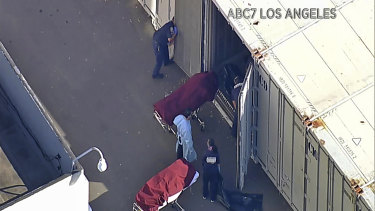 Workers put bodies into a refrigerated trailer at the offices of the Los Angeles County Coroner this month.