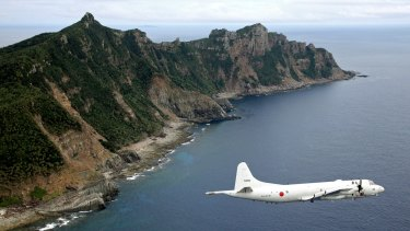 A Japan Maritime Self-Defence Force P-3C Orion surveillance plane flies over the disputed islands, called the Senkaku in Japan and Diaoyu in China.