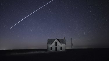 A string of SpaceX StarLink satellites passes over an old stone house near Florence, Kan. The train of lights was actually a series of relatively low-flying satellites launched by Elon Musk's SpaceX as part of its Starlink internet service.