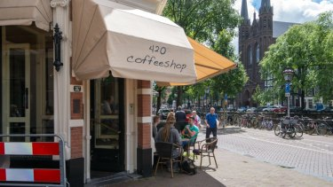 H8KX5C Amsterdam, Netherlands local coffee shop with people lounging outside. .