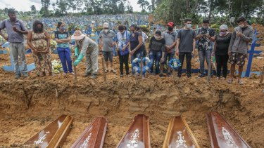 People wearing protective masks stand at the graves of their relatives at the Parque Taruma cemetery in Manaus, Brazil, during a mass burial of coronavirus victims.