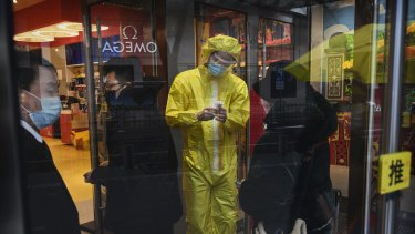 The temperatures of customers are checked in a shopping area in Beijing.