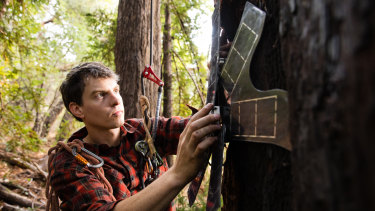 Topher White, chief executive of Rainforest Connection, attaches a modified smart phone powered by solar energy that will be used to detect illegal logging.