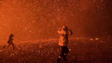 Firefighters run for safety as the Green Wattle Creek fire explodes into a sudden ember storm in Orangeville.