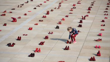 A child inspects an anti-domestic violence installation in which shoes represent abused women.