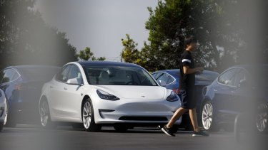 A person walks past a Tesla electric vehicle at the company's delivery center in Marina Del Rey, California.