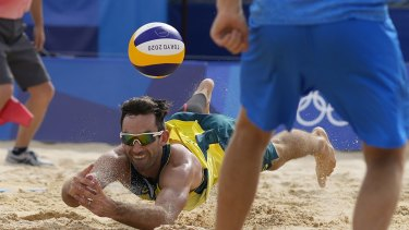 Damian Schumann, of Australia, dives for the ball during a men's beach volleyball match against the ROC team on Monday.
