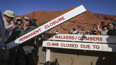 Ranger Lynda Wright places the new sign of the permanent closure of the Uluru climb.