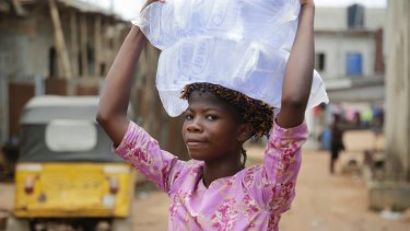Ripe for development and loans. A woman carry bags of sachet water she bought on a street in Baruwa Lagos, Nigeria.
