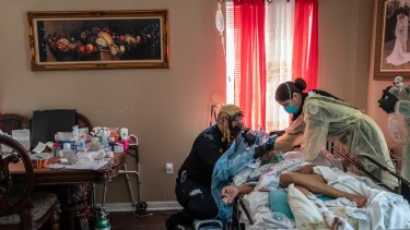 Medics intubate a gravely ill patient with COVID-19 symptoms at his home in New York in April 2020.