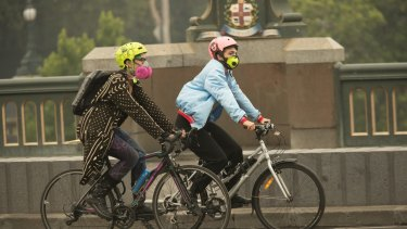 Cyclists ride over the Yarra as smoke blanketed Melbourne on Monday.
