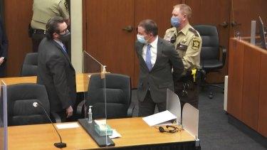 Derek Chauvin is taken into custody as his attorney, Eric Nelson, left, looks on.