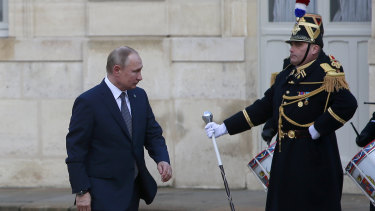 Russian President Vladimir Putin walks past Republican guards as he arrives at the Elysee Palace for Ukraine talks on Monday.