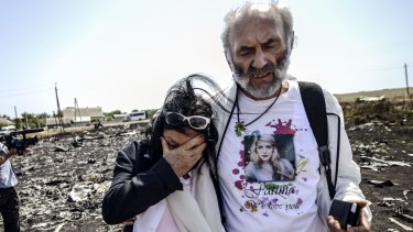 """Perth couple Jerzy """"George"""" Dyczynski and Angela Rudhart-Dyczynski look over the wreckage of the crashed aircraft in Ukraine."""