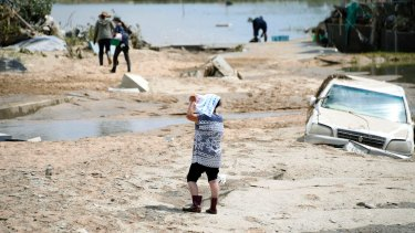 People walk around a housing area after flood waters receded in Kurashiki, Okayama prefecture, western Japan.