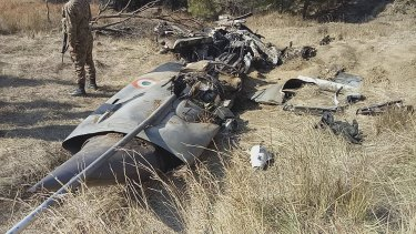 A Pakistani soldier stands guard near the wreckage of an Indian plane shot down by the Pakistan military.