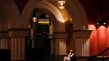 A woman talks on the phone in a normally busy Queen Victoria Building.