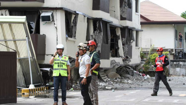 Rescue workers stand near an apartment block that partially collapsed after the strong earthquake in Davao City on Thursday.