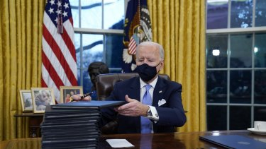 US President Joe Biden signs a flurry of executive orders in the Oval Office on his first day.
