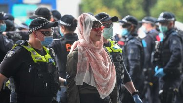 A woman is escorted to be fined at a makeshift police processing point at the United Petrol station on Kings Way on Friday.