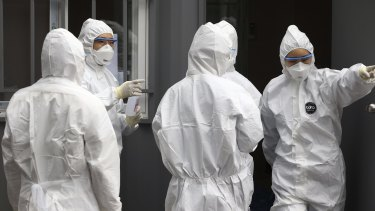 Officials wearing protective attire work to diagnose people with suspected symptoms of the virus in South Korea.