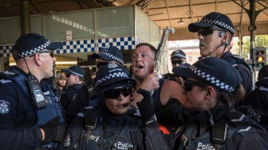 Police led a far-right nationalist away from Invasion Day protesters at Flinders Street Station.