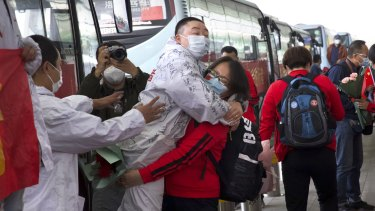 A medical worker, in red, embraces a colleague as she prepares to leave Wuhan after restrictions were lifted.