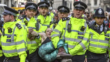 Police arrest protesters as they block traffic on London's Oxford Circus.