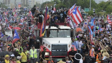 Puerto Rican singer Ricky Martin, front atop truck, participates with other local celebrities in a protest demanding the resignation of governor Ricardo Rossello in San Juan on Monday.