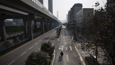 A man drags a handcart along a deserted road in Wuhan, Hubei province, China.