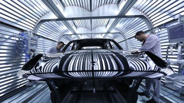 Workers perform quality checks on a Macan sports utility vehicle (SUV) in the light tunnel at the paint shop inside the Porsche Leipzig GmbH factory in Leipzig, Germany.