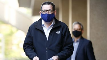 Victorian Premier Daniel Andrews wears a face mask as he walks into the daily government briefing on Sunday.