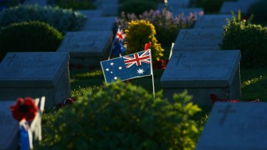 The last rays of the sun lights an Australian flag which has been placed on a grave at Lone pine in Gallipoli.