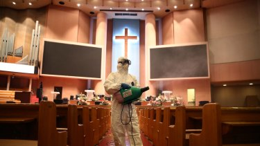 A disinfection worker wearing protective clothing sprays antiseptic solution in a South Korean church.