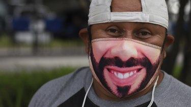 Fabian Santos, a street vendor and supporter of El Salvador's President Nayib Bukele poses with a Bukele mask outside a vaccination center in San Salvador, El Salvador.