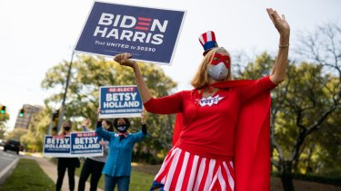 A person dressed in a 'Vote' superhero costume holds a campaign sign for Joe Biden outside a polling station in Atlanta, Georgia, on election day.