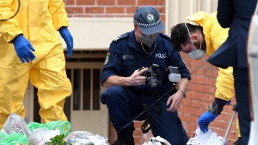 Police examine items outside Khaled Khayat's Lakemba unit as part of their investigation into an alleged terrorism plot.