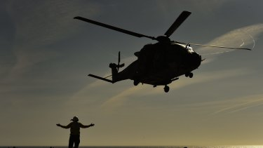 An Aviation support crew member signals during take off of a MRH90 or Taipan helicopter from 808 Squadron attatched to the HMAS Canberra in 2015.