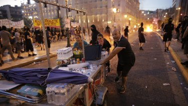Food vendors rush to clear the area in Syntagma Square during police clashes with protesters in central Athens, Greece, on Wednesday, July 15, 2015. Greek police clashed with protesters in central Athens as lawmakers debated a new bailout of up to 86 billion euros ($94 billion) that will impose further austerity on a country already ravaged by recession. Photographer: Matthew Lloyd/Bloomberg