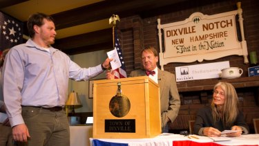Dixville Notch's first voter Clay Smith drops his ballot into the box as moderator Tom Tillotson watches.