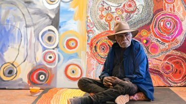 Ray Ken in front of works by Barbara Mbitjana Moore, Tjungkara Ken and Yaritji Young at Tjala Arts in Amata, South Australia.