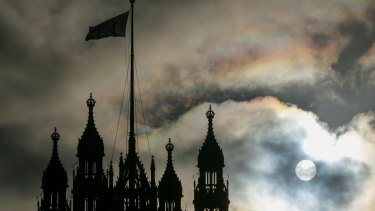 The sun breaks through clouds behind the Houses of Parliament in London.