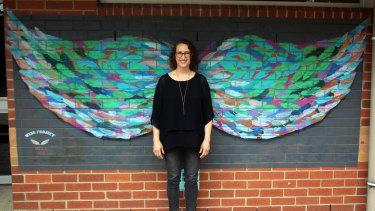Miriam Fee, standing before her winged artwork, teaches visual art at a Melbourne secondary school.