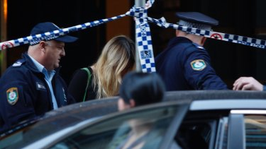 An unidentified woman is sheltered and led out of 118 Clarence Street after an alleged stabbing.