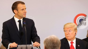 Emmanuel Macron delivers a speech while Donald Trump looks on at the Elysee Palace, in Paris, on November 11.