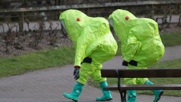 Personnel in hazmat suits walk away in Salisbury, England, after former Russian double agent Sergei Skripal and his daughter Yulia were found critically ill by exposure to a nerve agent.