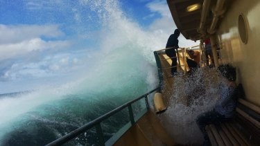 Tourists are soaked on a Manly ferry during a heavy swell.